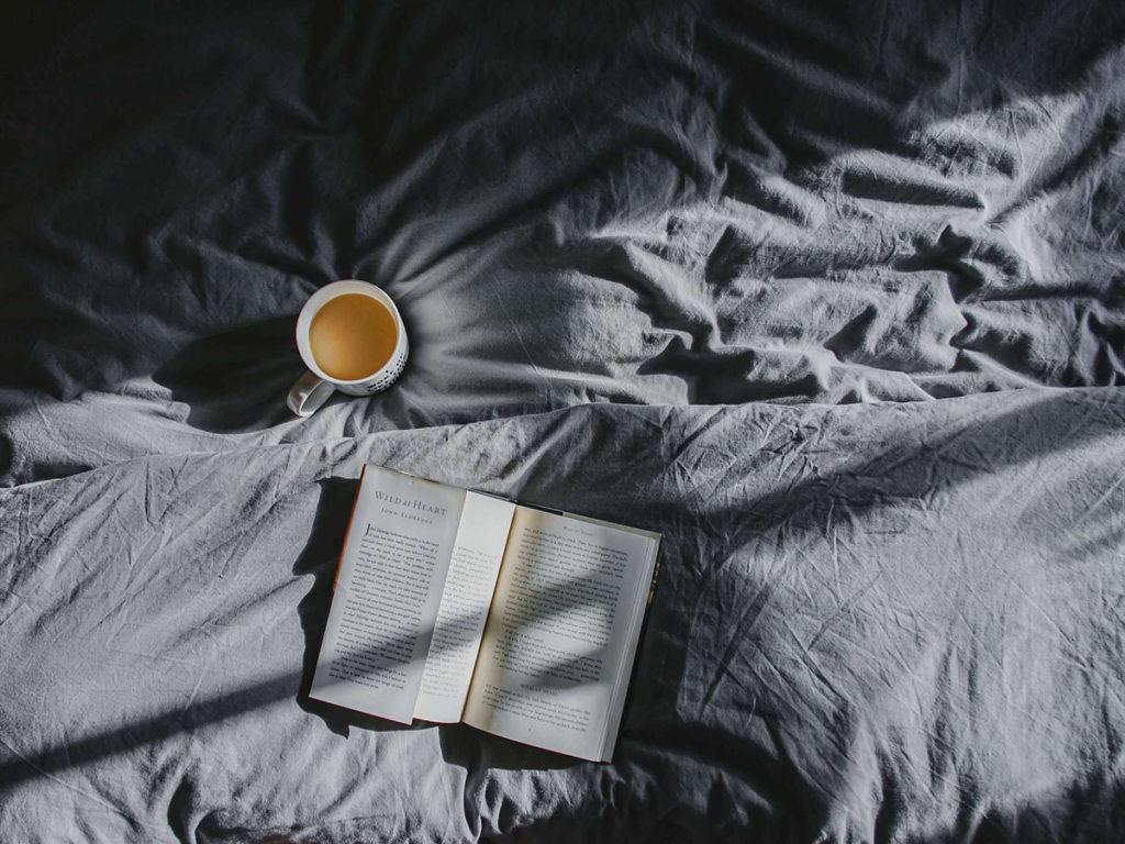 Libro y café sobre una cama deshecha para explicación de Que es Slow Life